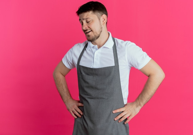 Парикмахер в фартуке выглядит усталым и скучающим с руками за бедра, стоящим над розовой стеной
