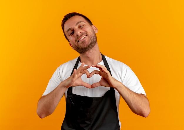 Парикмахер в фартуке, глядя вперед, весело улыбаясь, делая сердечный жест пальцами на груди, стоя над оранжевой стеной