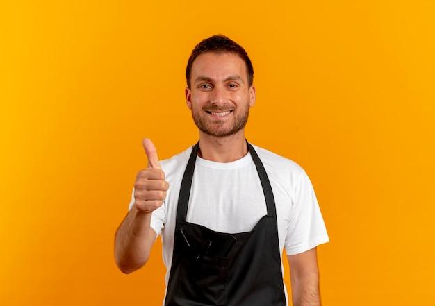 オレンジ色の壁の上に立って親指を見せてポジティブで幸せな笑顔を正面に見てエプロンの理髪店の男