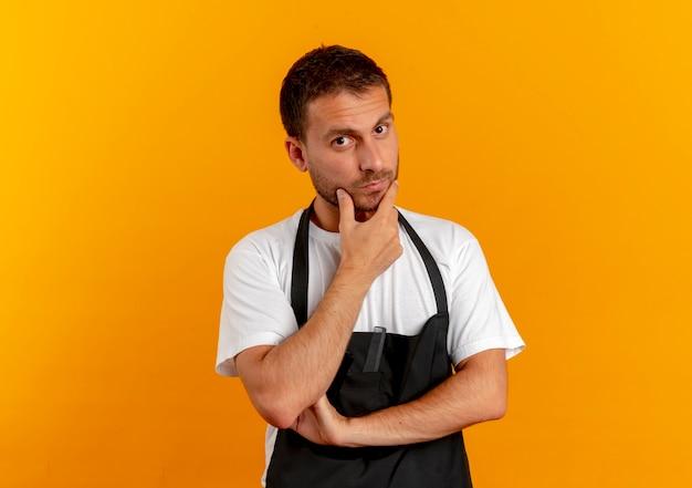 オレンジ色の壁の上に立って考えているあごに手を添えて正面を向いているエプロンの理髪店の男