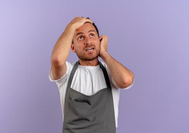 紫色の壁の上に立っている混乱した表情で見上げるエプロンの床屋の男