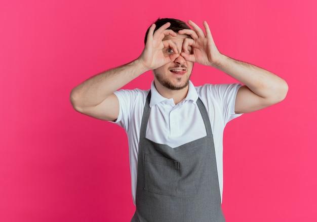 분홍색 배경 위에 서있는 웃는 손가락을 통해 찾고 손가락으로 쌍안경 제스처를 만드는 앞치마에 이발사 남자