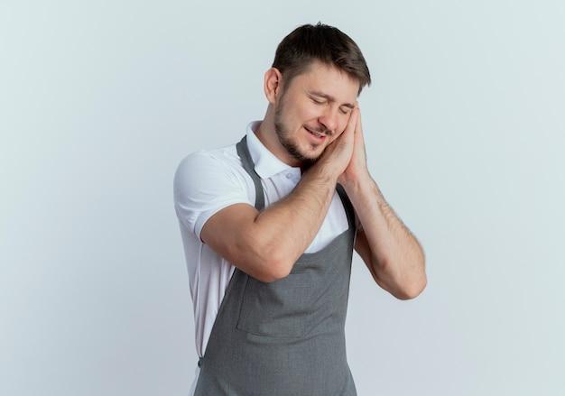흰 벽 위에 서있는 손바닥에 머리를 기대고 함께 손바닥을 들고 앞치마 만드는 수면 제스처에 이발사 남자