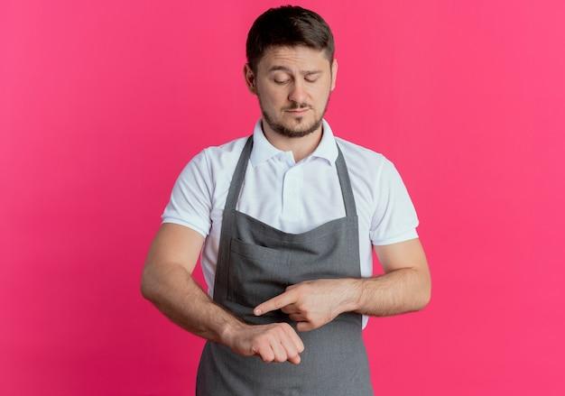 분홍색 배경 위에 서 심각한 얼굴로 시간에 대해 상기시키는 그의 팔을 가리키는 앞치마에 이발사 남자