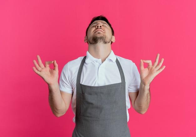 ピンクの背景の上に立って目を閉じて指で瞑想ジェスチャーを作るリラックスエプロンの理髪店の男