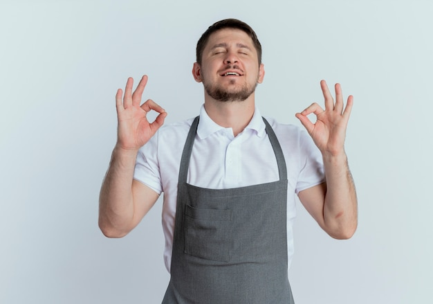 白い背景の上に立って目を閉じて指で瞑想ジェスチャーを作るリラックスエプロンの理髪店の男
