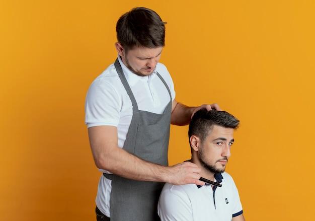 オレンジ色の壁の上の満足したクライアントのかみそりでひげを剃るエプロンの床屋の男