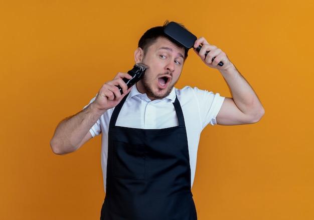 オレンジ色の壁の上に立っている彼の髪をとかすトリマーで彼のひげを剃るエプロンの床屋の男