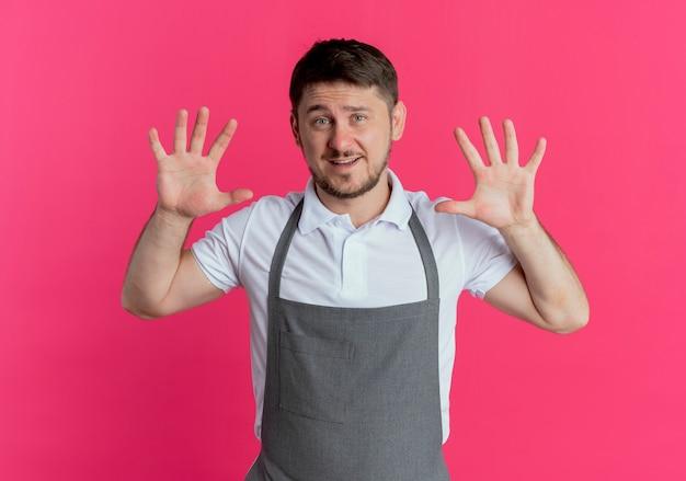 앞치마에 이발사 남자가 표시되고 분홍색 배경 위에 서있는 미소 10 번 손가락으로 가리키는