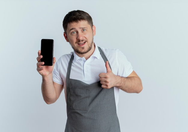 白い背景の上に立って自信を持って笑顔の親指を示すスマートフォンを示すエプロンの理髪店の男