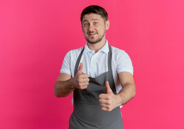 ピンクの壁の上に立って親指を見せて笑っているエプロンの床屋の男