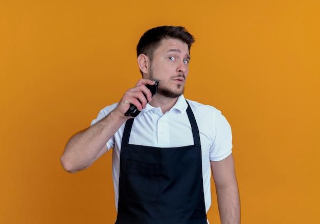オレンジ色の壁の上に立っている彼のひげをトリミングするエプロンの床屋の男
