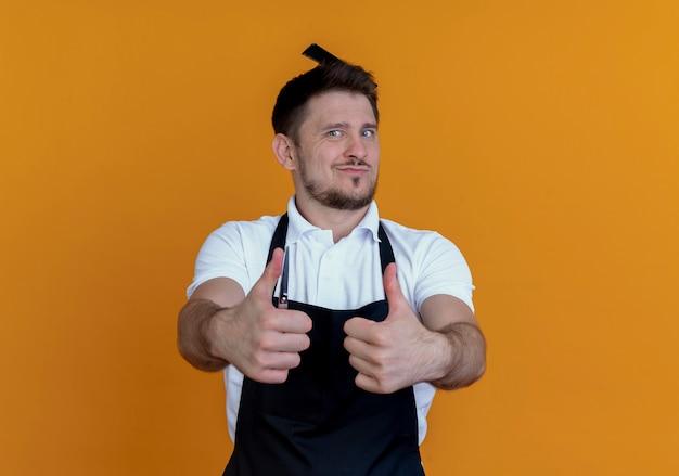 オレンジ色の背景の上に立って親指を示すカメラを見て彼の髪にヘアブラシでエプロンの理髪店の男