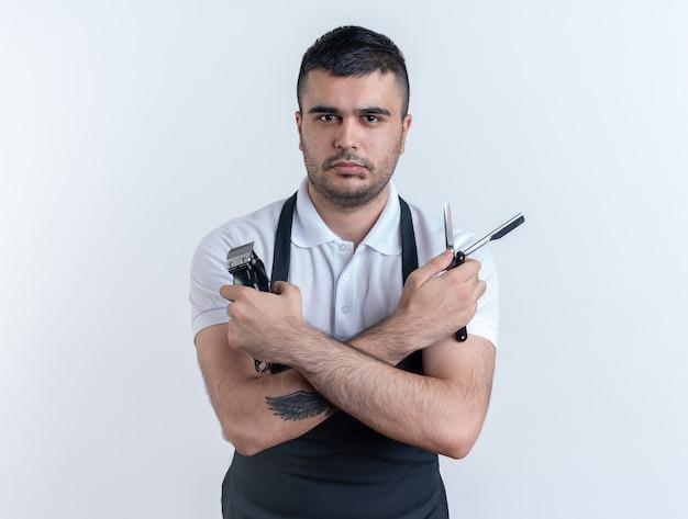白い背景の上に立っている真剣な自信を持って表情でカメラを見ている美容ツールとエプロンの理髪店の男