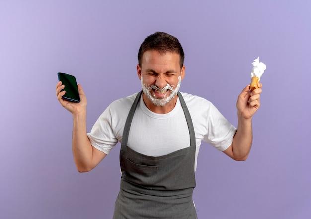 スマートフォンを保持し、紫色の壁の上に興奮して幸せそうに見えるシェービングブラシを顔にシェービングフォームでエプロンの理髪店の男