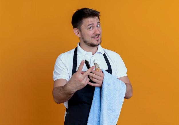 泡とかみそりでシェービングブラシを持って手にタオルを持ったエプロンの床屋の男が自信を持ってカメラを見て、オレンジ色の背景の上に立っている2番目を示しています