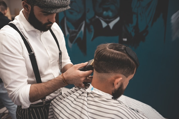 Barber man shaves client in barbershop.