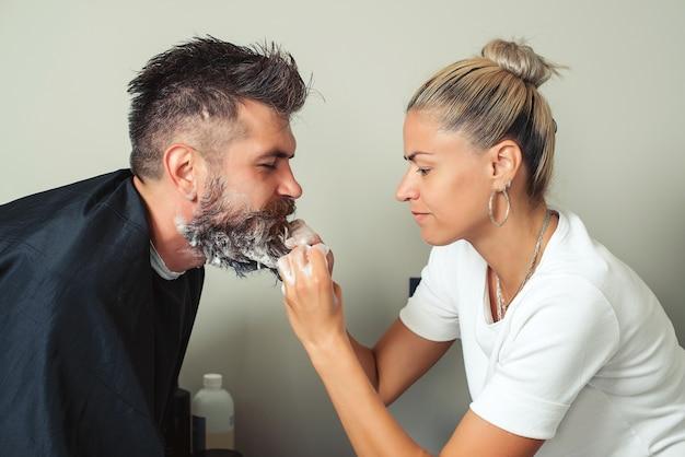 이발사는 이발소에 있는 힙스터 남자의 검은 색으로 수염과 콧수염을 칠합니다. 미용사 미용사 세척 고객 수염 - 미용 미용실에서 휴식을 취하는 남자. 수염 이발소 청소.