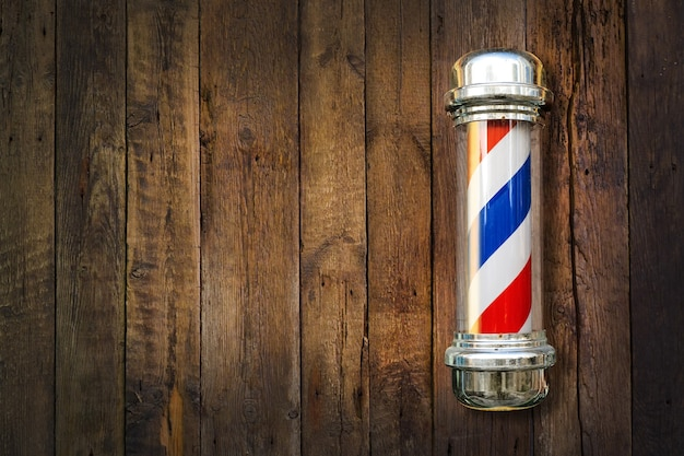 Парикмахерская. полюс парикмахерской на деревянном фоне с копией пространства.