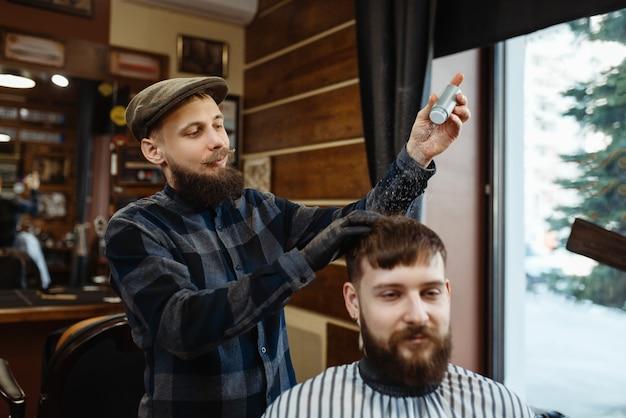 理髪師はクライアントの髪にムースを置きます。プロの理髪店は流行の職業です