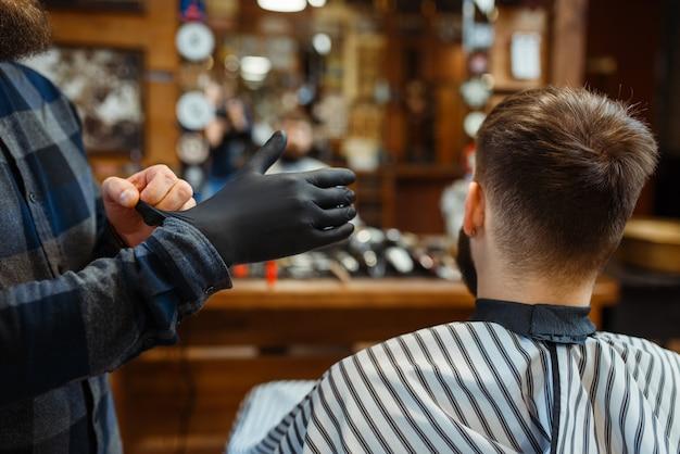 Парикмахер надевает перчатки, клиент сидит в кресле. профессиональная парикмахерская - модное занятие. мужской парикмахер и клиент в парикмахерской
