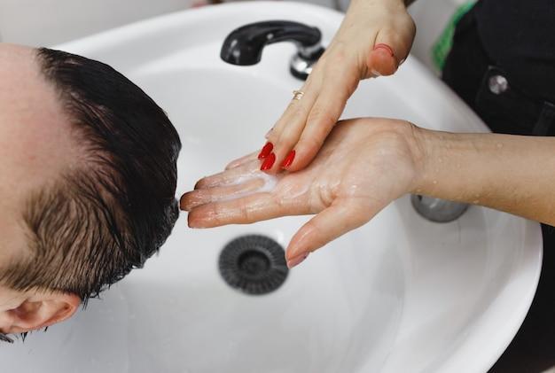 고객의 머리를 클로즈업하는 이발사의 손. 머리카락에 샴푸 바르기.