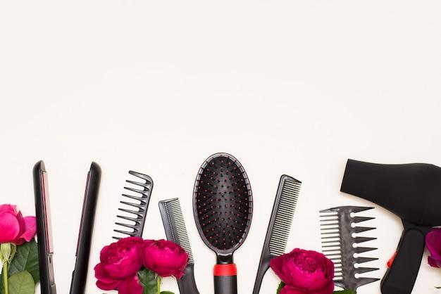 Комплект парикмахера различных щеток и фена для волос с розовыми розами на белой предпосылке с космосом экземпляра.