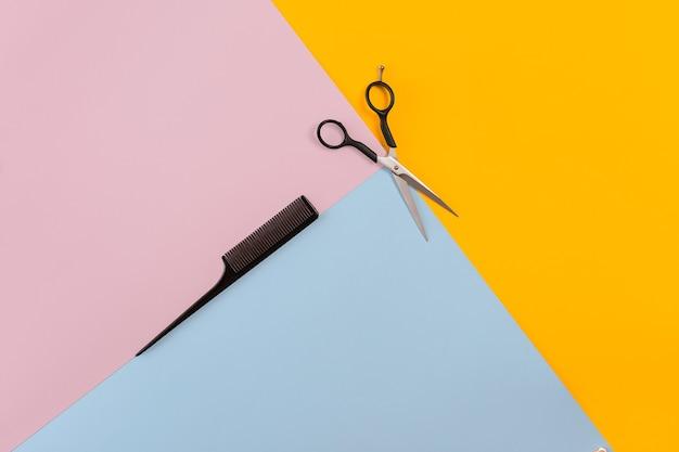 Набор парикмахера с расческой и ножницами на цветном розовом, желтом, синем бумажном фоне. вид сверху. скопируйте пространство. натюрморт. макет. плоская планировка