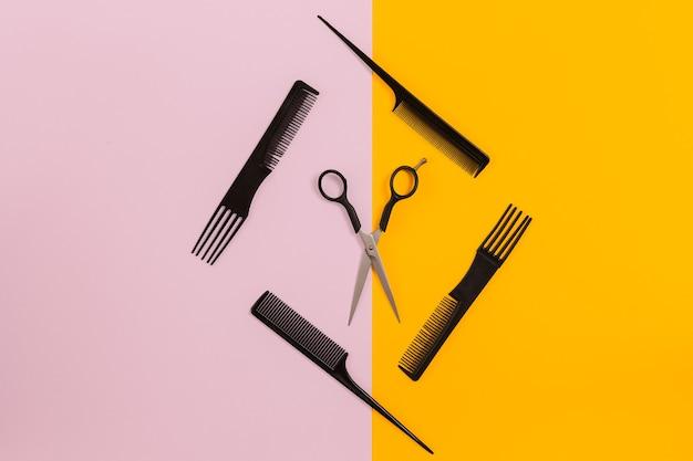 Парикмахерская с гребнями и ножницами на розовом и желтом фоне. вид сверху. скопируйте пространство. натюрморт. макет. плоская планировка