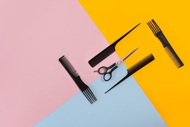 Парикмахерская с гребнями и ножницами на розовом, желтом, синем бумажном фоне. вид сверху. скопируйте пространство. натюрморт. макет. плоская планировка