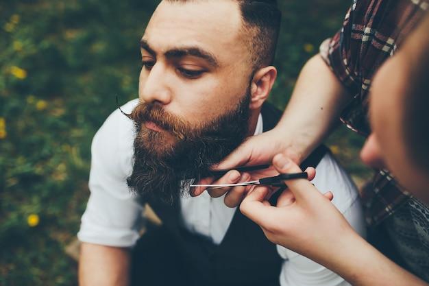 이발사는 빈티지 분위기에서 수염 난 남자를 면도