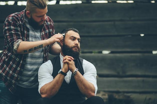 Парикмахер бреет бородатого мужчину в винтажной атмосфере