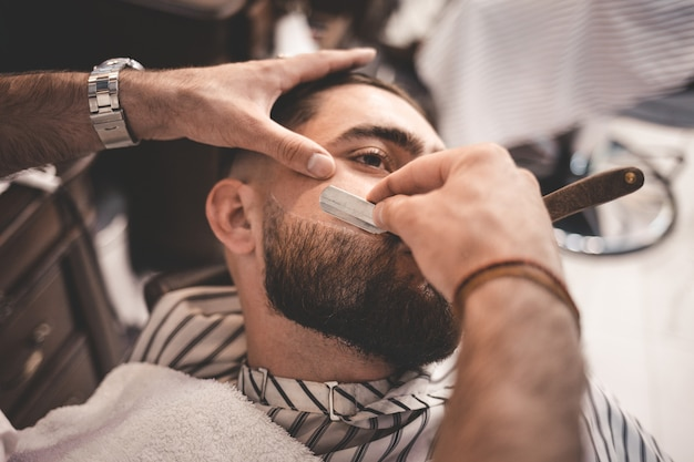Barber shaves the beard of the client