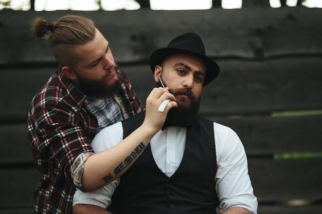 Il barbiere rade un uomo barbuto in un'atmosfera vintage