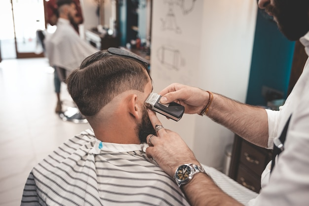 Barber shaves client in barbershop