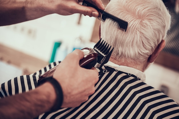 Barber shaves grey haired adult nape with razor