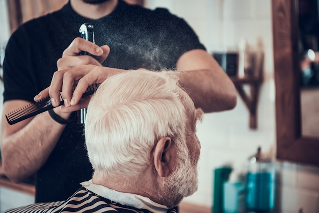 Barber shaves grey haired adult sides with razor