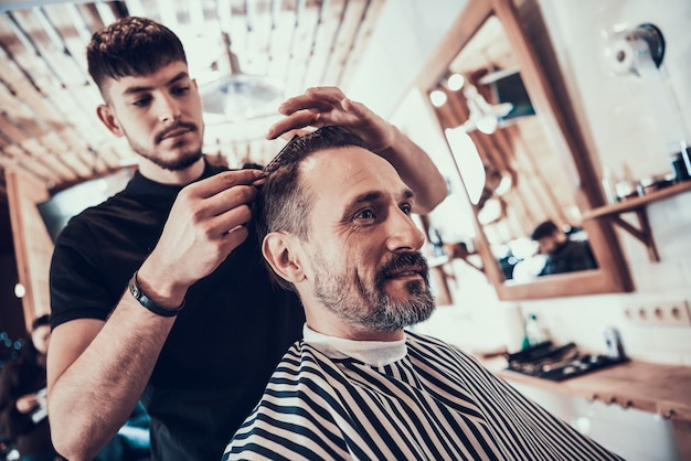 Barber shaves handsome smiling man with razor.