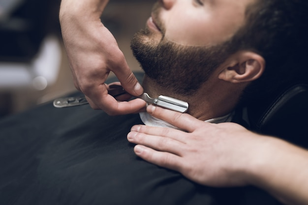Barber shaves his head, mustache and beard to man