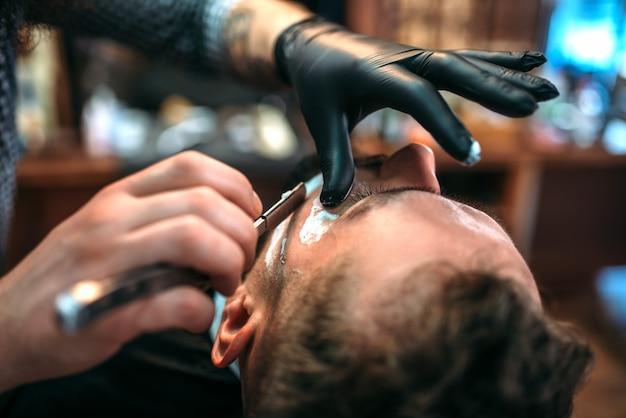理髪師は理髪店でかみそりでひげを剃ります。