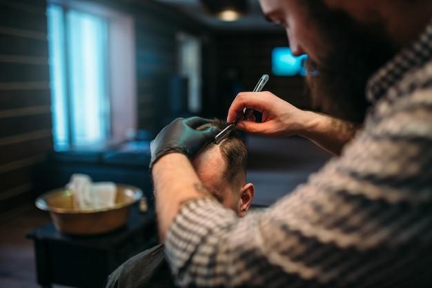 Парикмахер бреет волосы опасной бритвой. мужчина-клиент в парикмахерской.