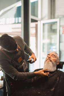Barber shaving beard to elderly man