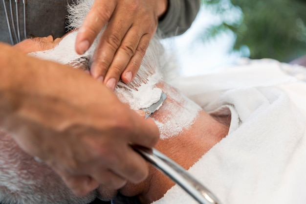 Barber shaving beard to man in salon