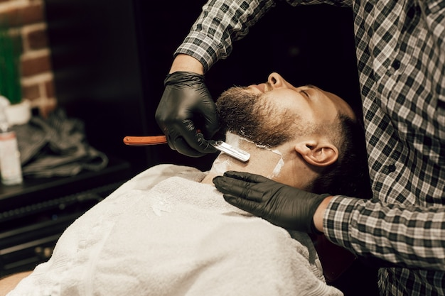 Barber shaving a bearded man in a barber shop. close up of a hairdresser's hands in black gloves shaving a client's beard.