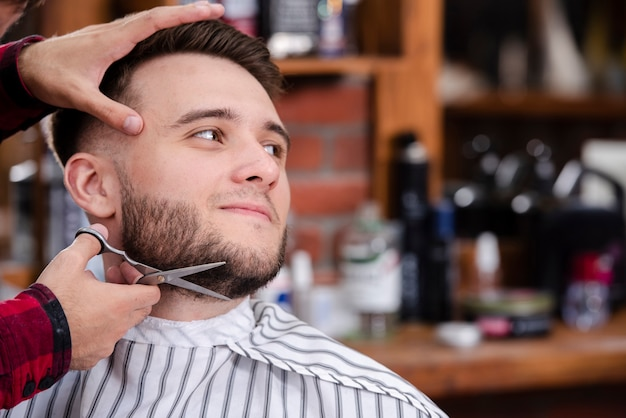 Barber shaving beards man in barber shop