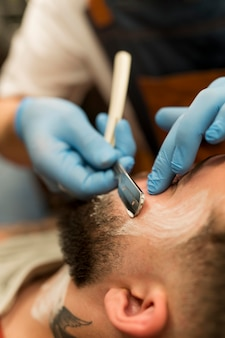 Barbiere che rade e modella la barba del cliente maschio male