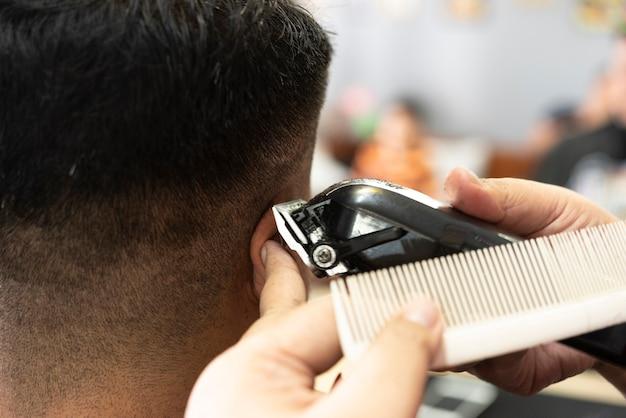이발소에서 전문 전기 깎기로 머리카락을 면도하는 이발사
