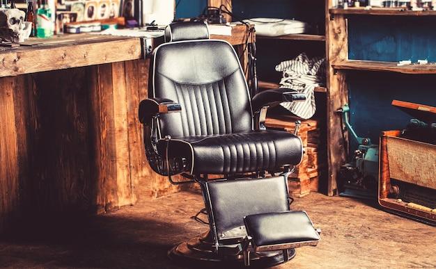 Стул парикмахерской. кресло парикмахерской, современная парикмахерская и парикмахерская, мужская парикмахерская. стильное винтажное кресло для парикмахера. профессиональный парикмахер в интерьере парикмахерской.