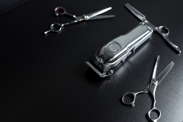 Barber shop equipment on black background with place for text. professional hairdressing tools. comb, scissor, clippers and hair trimmer isolated