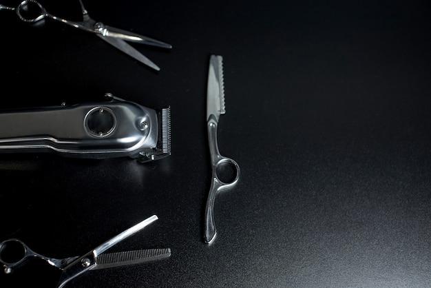 テキストのための場所と黒の背景に理髪店の機器。プロの理髪ツール。櫛、はさみ、バリカン、ヘアトリマーの絶縁